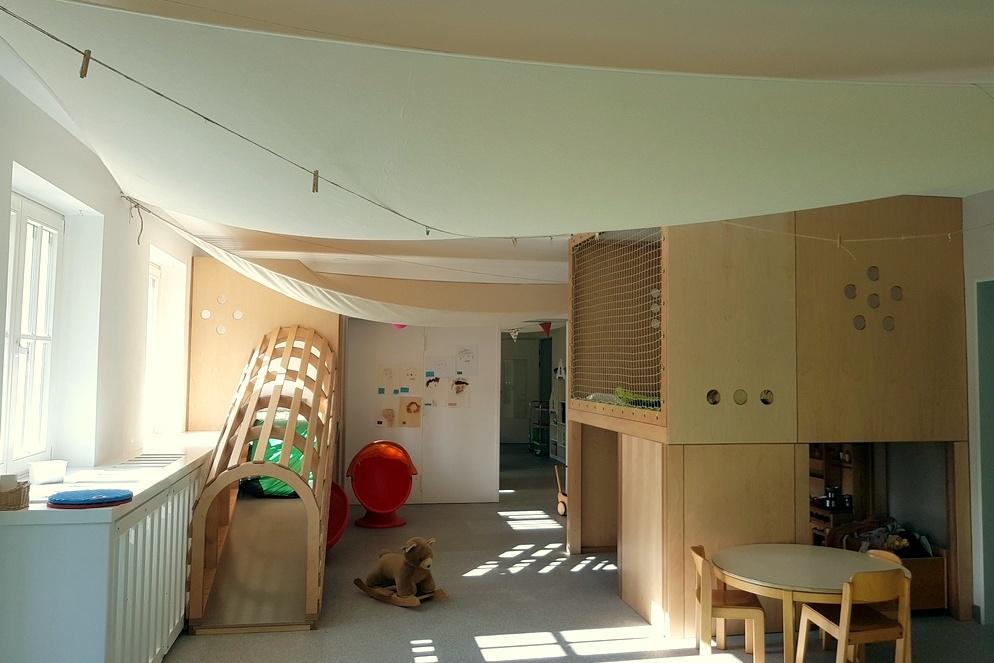 Ein Teil des sehr grossen Gruppenraumes mit Möbeln, die wir nach eigenen Wünschen haben schhreinern lassen. Auf der Rampe links können auch die kleinen Krabbelkinder hoch zum Fenster. Rechts unser Hochpodest mit darunter liegender Küche. Schallschutzsegel sorgen dafür, dass wir eine sehr gute Schalldämmung haben.